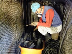炭焼き窯  中で割る作業の写真